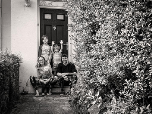 Black and white portrait of a family sitting on the doorstep