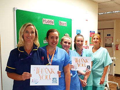 Group of nurses hold up a Thank You sign