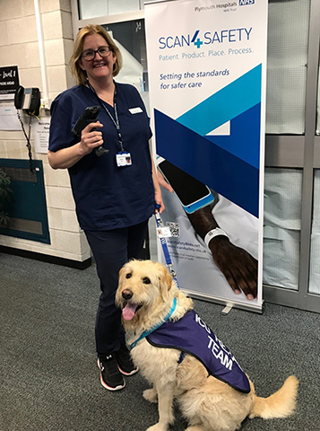 Senior ICU Sister Kate Tantam holding a Scan4Safety handheld barcode scanner and Hovis the Therapy Dog
